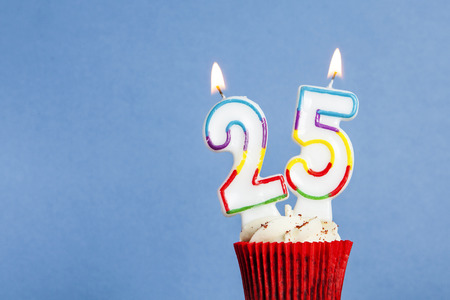 Photo for Number 25 birthday candle in a cupcake against a blue background - Royalty Free Image