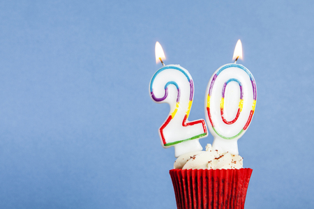 Photo pour Number 20 birthday candle in a cupcake against a blue background - image libre de droit