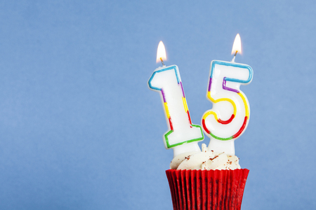 Photo pour Number 15 birthday candle in a cupcake against a blue background - image libre de droit