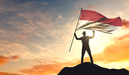 Photo for Indonesia flag being waved by a man celebrating success at the top of a mountain. 3D Rendering - Royalty Free Image