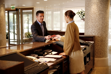 Photo for Man checking in at hotel reception desk - Royalty Free Image