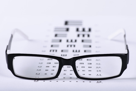 Photo pour Reading black eyeglasses and eye chart close-up on a light background - image libre de droit