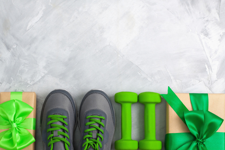 Photo pour Holiday christmas birthday party sport flat lay composition with gray shoes, green dumbbells  and craft gifts with green bow on gray concrete background. Top view, horizontal orientation - image libre de droit