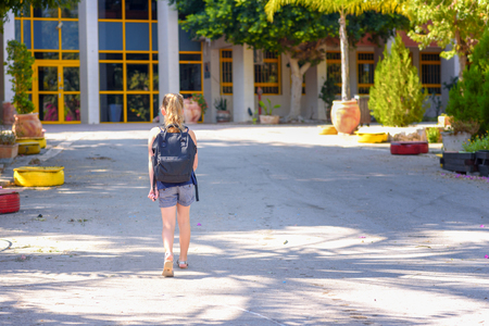 Foto de Happy kid Back to school. Child little girl with bag go to elementary school. Child of primary school. Pupil go study with backpack. Back View. - Imagen libre de derechos