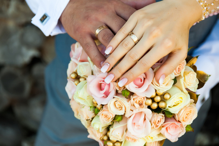Photo for Close-up of hands of the groom and bride, against the background of a colorful bouquet. - Royalty Free Image