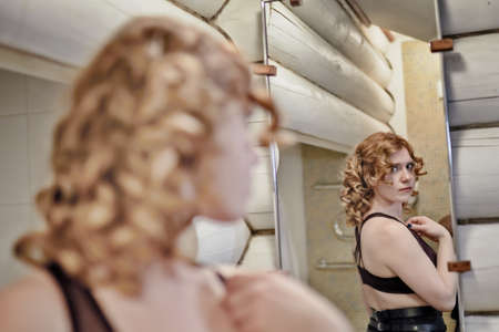 Photo for Curly hair redheaded young woman looking at herself in the mirror in the bathroom - Royalty Free Image