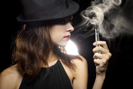 Photo pour woman smoking or vaping an electronic cigarette to quit tobacco - image libre de droit