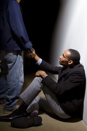 Photo for man helping a depressed fellow by offering a helping hand - Royalty Free Image