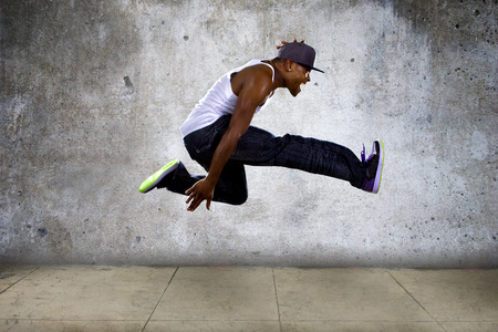 Photo pour Black urban hip hop dancer jumping high on a concrete background - image libre de droit
