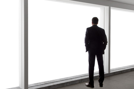 Photo for Middle aged businessman looking out a bright office window and thinking - Royalty Free Image