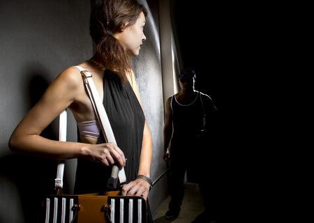 Foto de woman using a pepperspray for self defense against mugger in a dark alley - Imagen libre de derechos