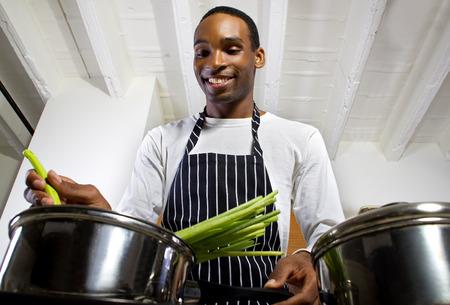 Foto de close up of a young black man wearing an apron and cooking at home - Imagen libre de derechos