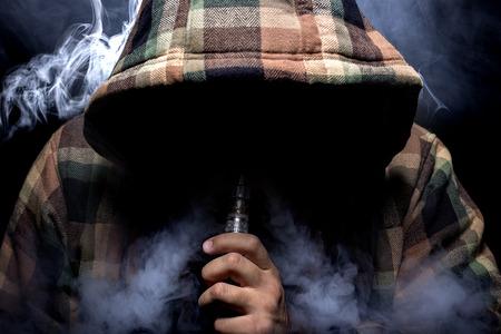 Foto de Man with concealed identity smoking a controversial vape is a health risk - Imagen libre de derechos