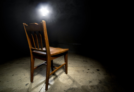 Photo for Isolated wooden chair in a dark scary prison with an interrogation spotlight - Royalty Free Image