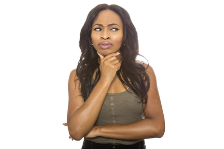 Foto de Black female isolated on a white background displaying facial confused expressions.  She is young and of African American ethnicity. - Imagen libre de derechos