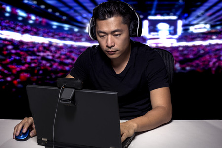 Photo pour Competitive asian male professional E Sports video gamer playing an FPS, or MMO game on a computer and streaming online. - image libre de droit