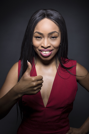 Photo for Black female model on a dark background with approval expressions. She is holding her thumbs up. - Royalty Free Image
