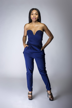 Foto de Sexy black female fashion model wearing apparel with blue pants.  The outfit is modern style for spring or summer clothing collection. The image depicts trends in womenswear - Imagen libre de derechos