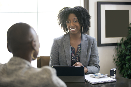Photo pour Black female businesswoman in an office with a client giving legal advice about taxes or financial loans. The woman could be a lawyer or a cpa accountant. - image libre de droit