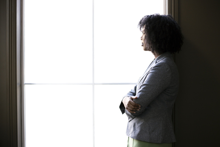 Photo for Silhouette of a black African American businesswoman thinking by the office window. She is brainstorming or planning for her startup business. - Royalty Free Image