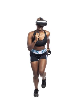 Photo pour Black African American female running in VR while wearing a virtual reality headset for training or playing a video game.  Depicts technology and sport and esports. - image libre de droit