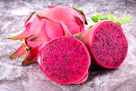 Foto de Beautiful fresh red dragon fruit (pitaya) on stone background - Imagen libre de derechos
