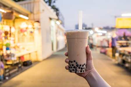 Photo pour A young woman is holding a plastic cup of bubble milk tea with a straw at a night market in Taiwan, Taiwan delicacy, close up. - image libre de droit
