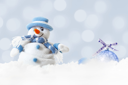 Photo pour Christmas happy snowman wearing blue hat and scarf with xmas balls on abstract lights background, white soft snowflakes falling on winter landscape, merry Christmas and happy new year greeting card - image libre de droit