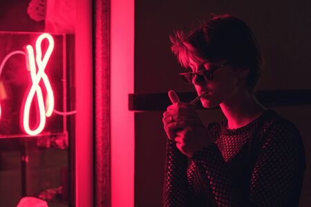 Photo for Fashion sexy tomboy hipster woman smoke cigarette in city neon night red light - Royalty Free Image