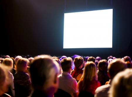 Photo pour Crowd audience in dark looking at bright screen - image libre de droit