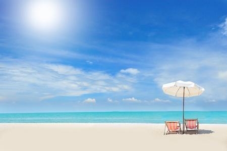 Beach chairs on the white sand beach with cloudy blue sky