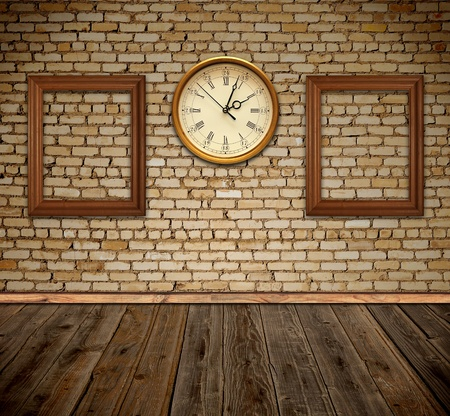 empty photo frames and wall clock against an wall in old room
