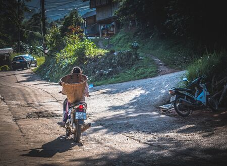 Foto de Hilltribe on a bike taking coffee beans to local roaster in Mae Wang, Chiang Mai - Thailand. - Imagen libre de derechos
