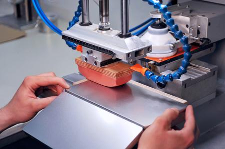Foto de Somebody is working with a pad printer - printing on a tin - Imagen libre de derechos