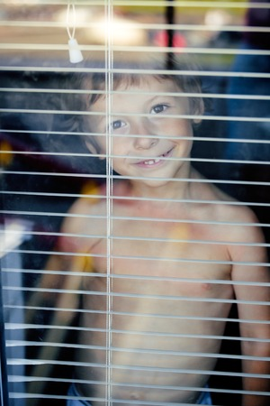Little cute boy throught window making faces close up