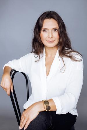 Photo pour pretty brunette confident mature woman sitting on chair in studio - image libre de droit