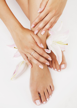 Photo pour manicure pedicure with flower lily close up isolated on white perfect shape hands spa salon - image libre de droit