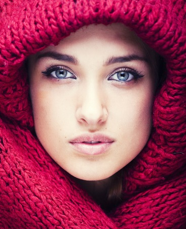 young pretty woman in sweater and scarf all over her face, soft lips close up