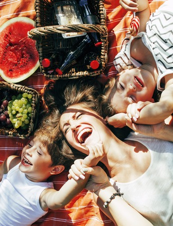 Photo pour cute happy family on picnic laying on green grass mother and kids, warm summer vacations close up, brother and sisterhood - image libre de droit