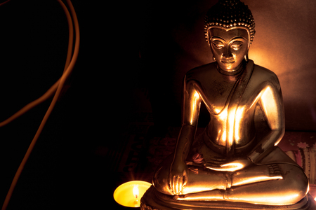 Photo pour Selective focus of buddha statue with blurred burning candle light in soft night light with line light . Concept of peace, meditation, hope and relaxation. - image libre de droit