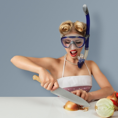Young blonde woman cutting onion in diving scuba mask for protect eyes