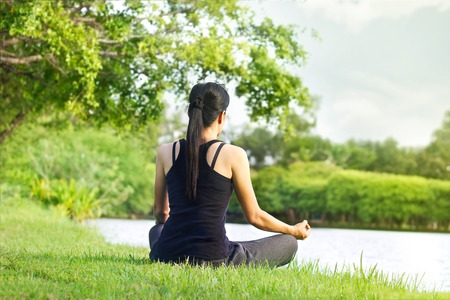 Photo pour Sport girl meditating in nature green park at the sunrise - image libre de droit