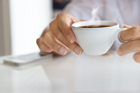 Foto de businessman and a cup of coffee in hand, blank text and soft focus - Imagen libre de derechos
