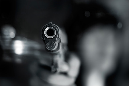 Photo pour Black and white, woman pointing a old gun to front with one Hand on dark background - image libre de droit