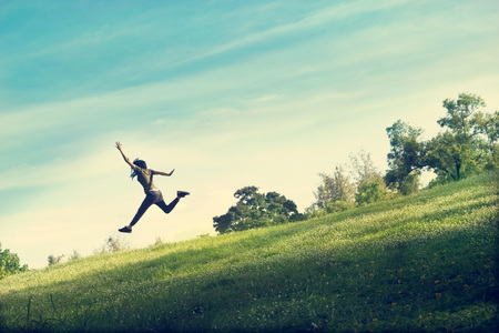 Foto de woman running and jumping funny relax on green grass and flower field - Imagen libre de derechos