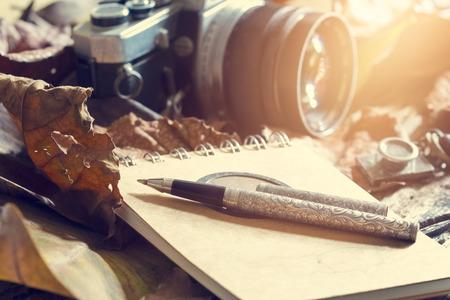 Foto de Retro pen on old note pad and camera on dry leaf in jungle background, Vintage color tone - Imagen libre de derechos