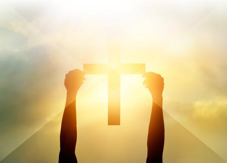 Photo pour Silhouette the cross in hands, religion symbol in light and landscape over a sunrise, background, religious, faith concept - image libre de droit
