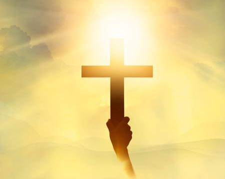 Foto de Silhouette the cross in hand, religion symbol in light and landscape over a sunrise, background, religious, faith concept - Imagen libre de derechos