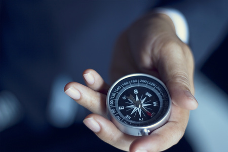 Foto de Businessman with a compass holding in hand, color tone film look - Imagen libre de derechos