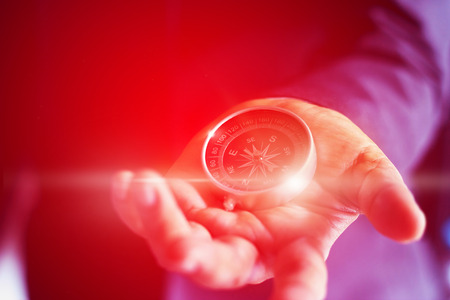 Abstract, colorful businessman with a compass holding in hand, soft focus